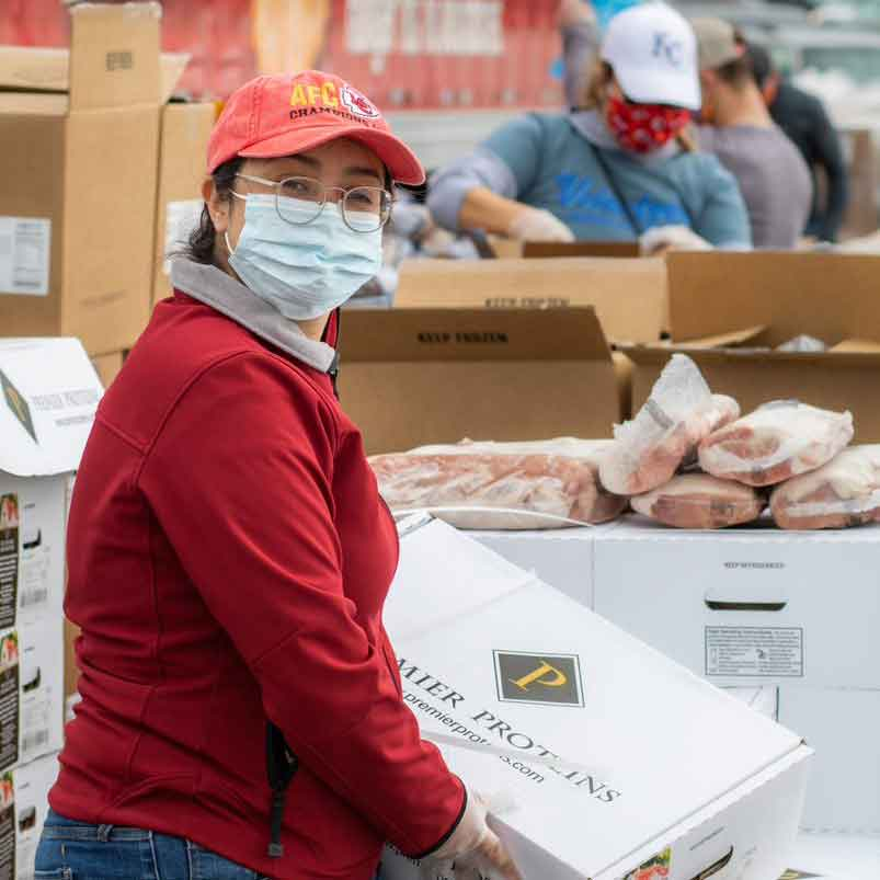 woman wearing mask carrying box of food