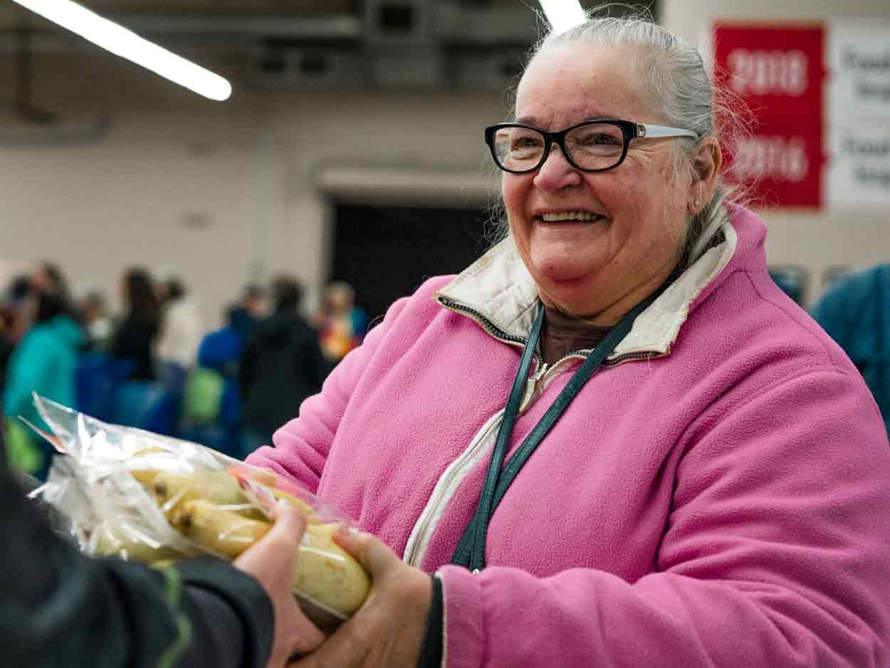 smiling woman holding package of vegetables