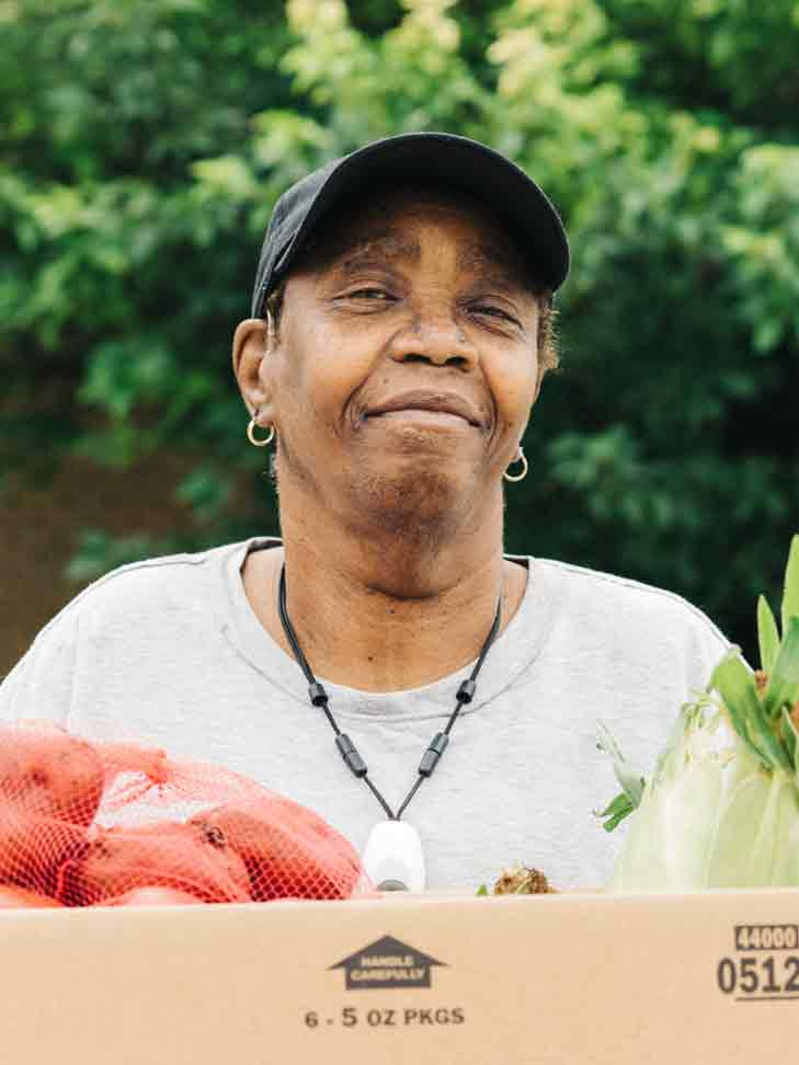 smiling woman holding box of fresh vegetables
