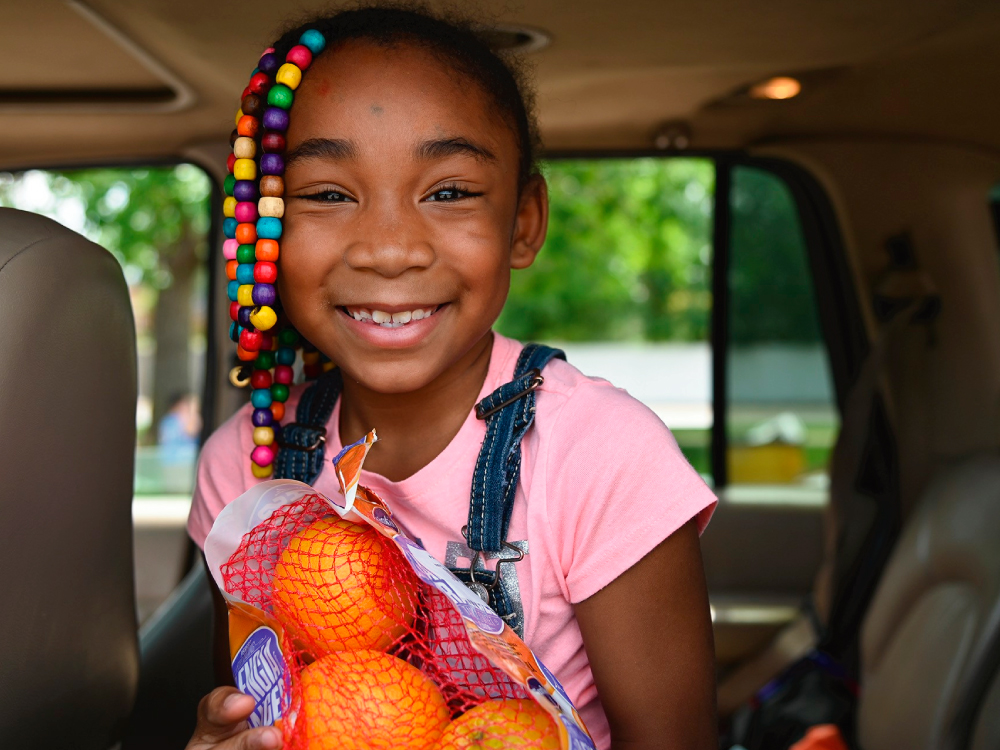 Young Girl Holding Oranges in Car