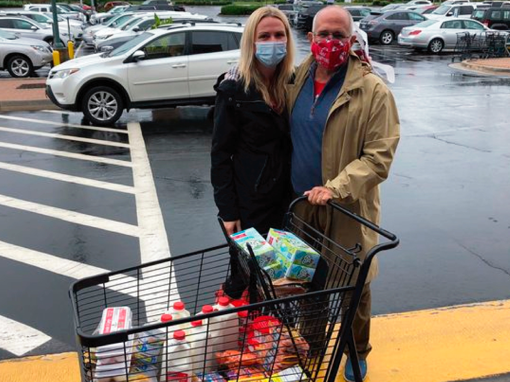 Couple with Food Donations at Fill the Fridge
