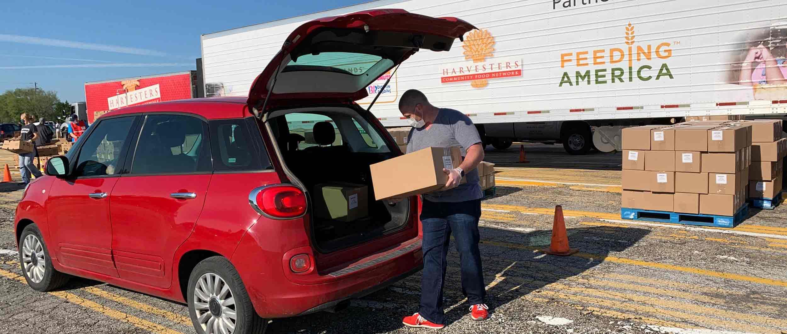 Man putting box of food in car
