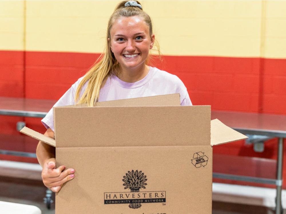 Girl Folding Harvesters Box