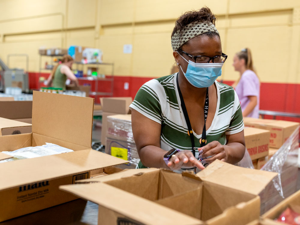 Woman Packing Box in Warehouse